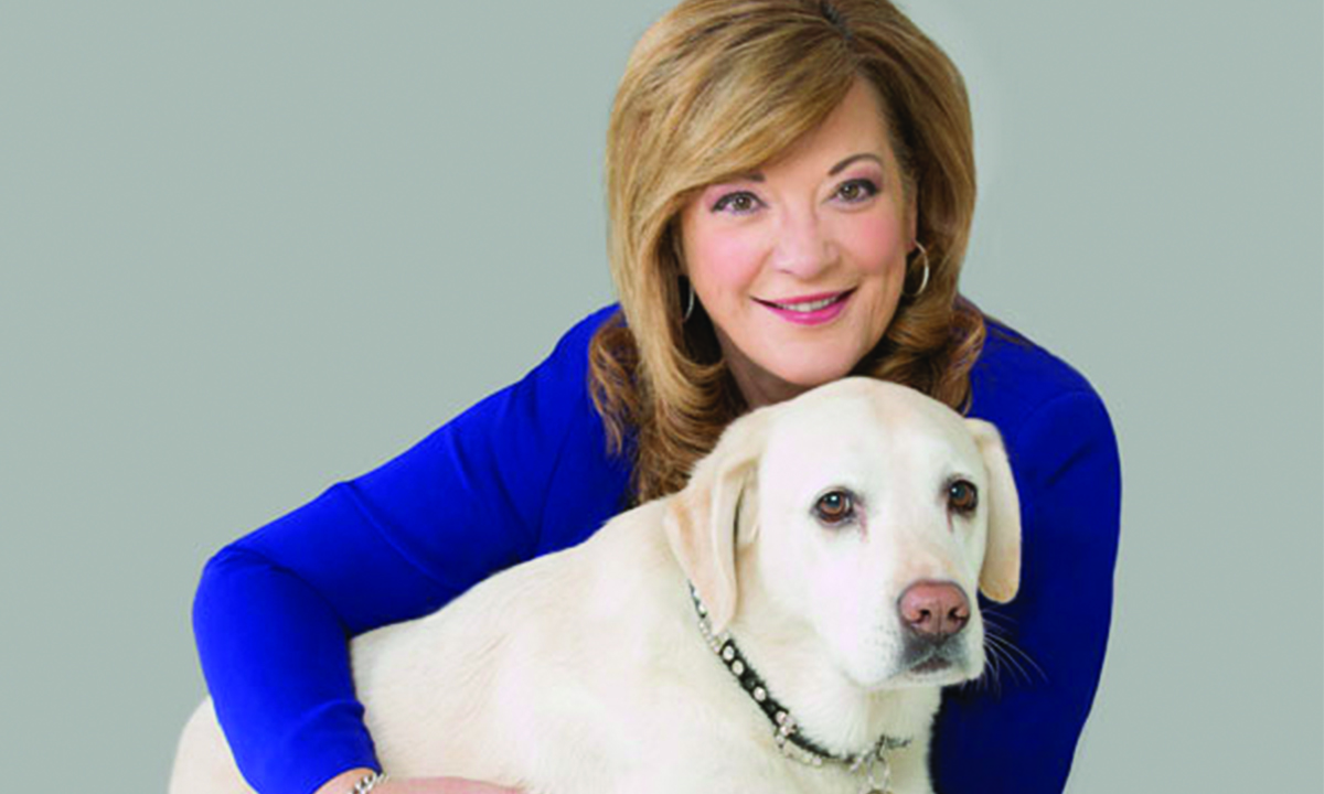Karen Hayes has her arm around her yellow ambassador dog, Willow.