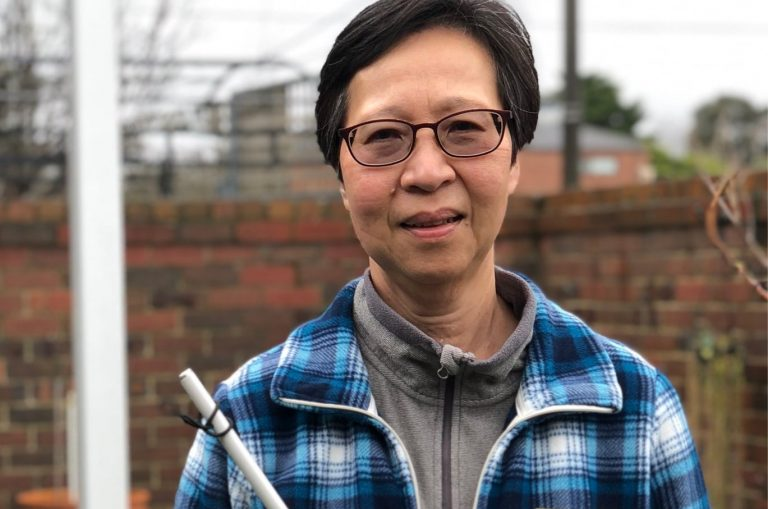 A person standing outside smiling at the camera while holding their white cane.
