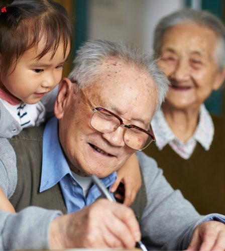 An older man writing while a young girl puts her arms around his shoulders, hugging him. The man is smiling and there is an older woman in the background who is not in focus but is also smiling.