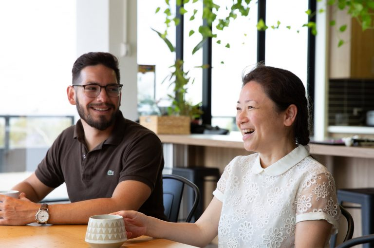Two people sitting at cafe table. Both people are smiling.