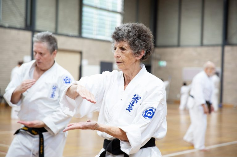 Two people at an indoor karate class. Both are in a karate uniform and are holding their hands in a karate pose.