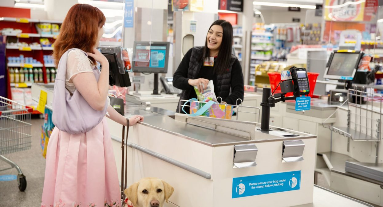 A person at a check out who is looking at the cashier. The cashier is smiling. The person at the checkout has a yellow labrador Guide Dog in harness who is looking at the camera.