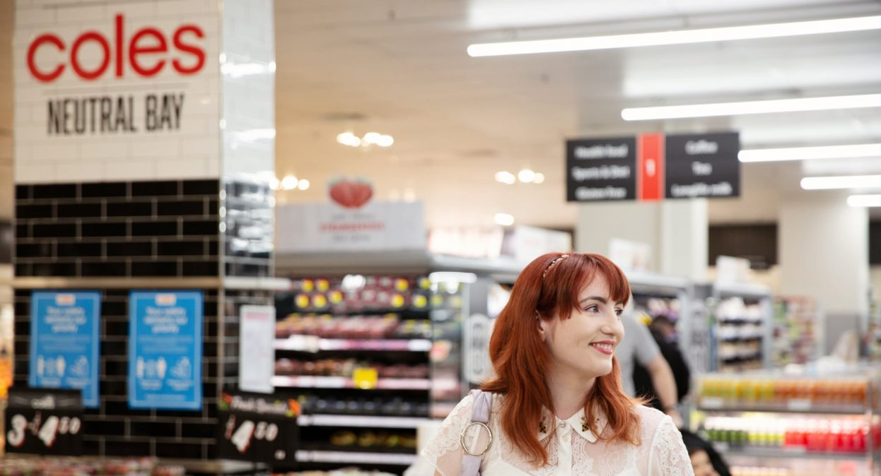 A person at in a supermarket. They are smiling and looking to the right of the camera.